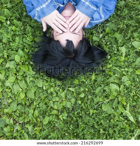 Young woman lying on the grass covers his eyes with his hands, top view with space for text.