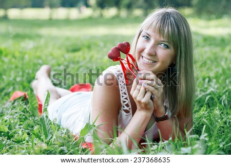 young woman lying on the grass in the park and holds two hearts