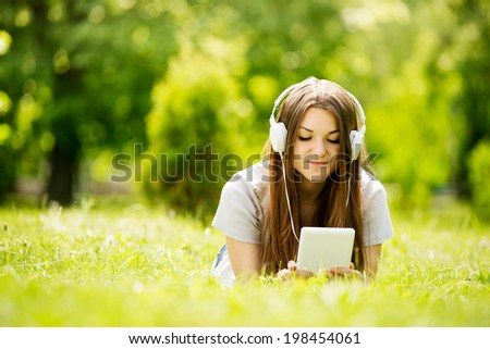Young woman lying on the grass listening to music on her headphones that she has downloaded onto her tablet or MP3 player as she enjoys the tranquility of a lush green park - stock photo
