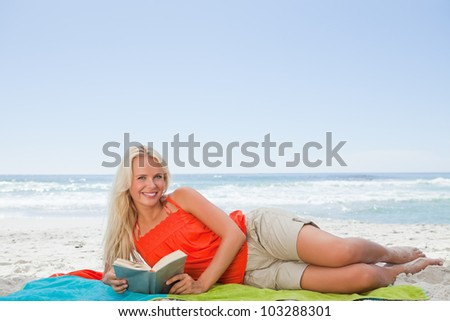 Young woman lying on the side while looking at the camera and holding a book