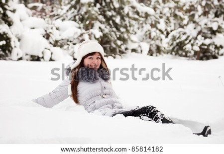 Young woman lying on the  snow in winter - stock photo