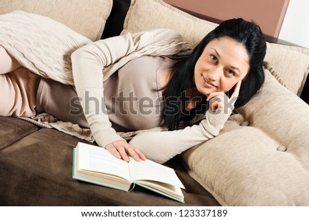 Young woman lying on the sofa and reading a book,Woman with a book - stock photo