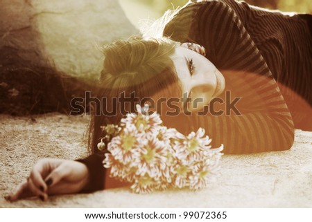 Young woman lying on the tombstone - stock photo