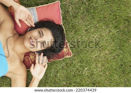 Young woman lying outside listening to music - stock photo