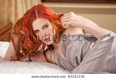 Young woman lying seductively on the hotel bed - stock photo