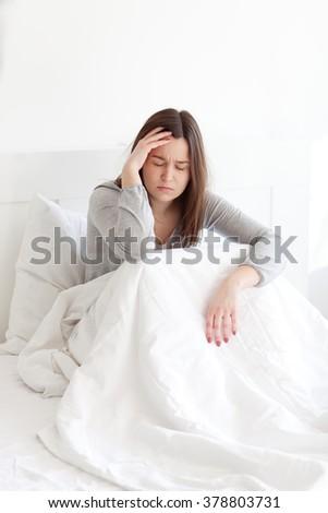 Young woman lying sick in bed having headache - stock photo