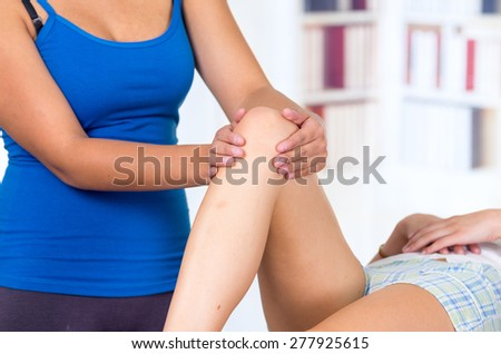 young woman lying while getting a leg massage from specialist concept of physiotherapy