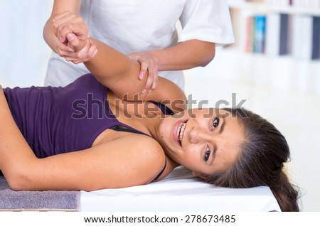 young woman lying while getting an arm massage from specialist concept of physiotherapy - stock photo