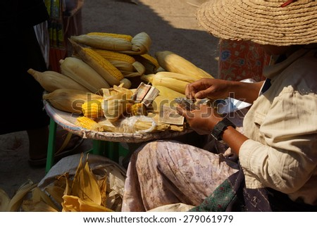 Young woman makes change while selling roasted corn on the cob,  Inle Lake,  Myanmar (Burma) - stock photo