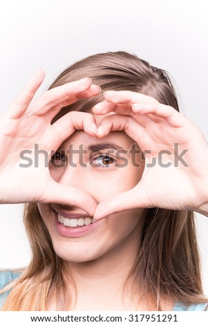 Young Woman Makes Hands Heart Shape and Smiling