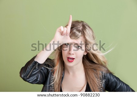 Young woman makes loser sign on her forehead over green background - stock photo