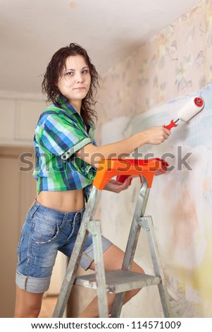 Young woman makes repairs in the apartment
