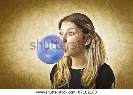 Young woman making a big bubble with a chewing gum