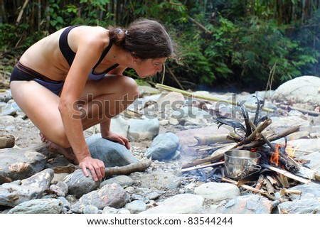 Young woman making a fire on pebble beach - stock photo
