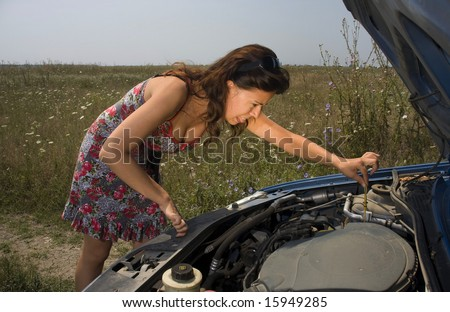 young woman making a funny face while trying to fix a broken car
