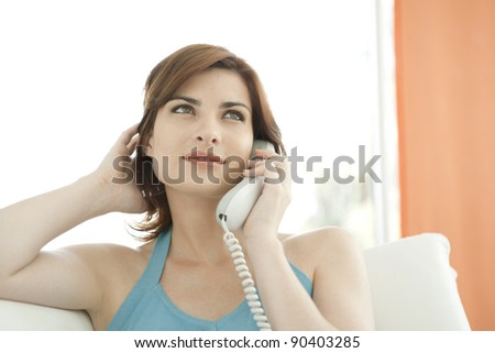 Young woman making a phone call at home while sitting on a sofa.