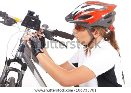Young woman making an adjustment in her bike - stock photo