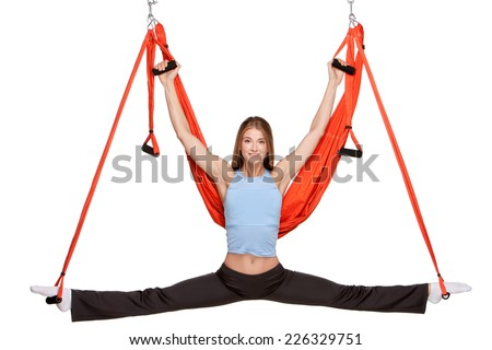 Young woman making antigravity yoga exercises in stretching twine with red hammock on a white background