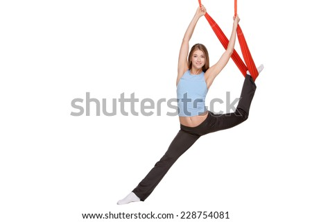 Young woman making antigravity yoga exercises with red hammock on a white background - stock photo