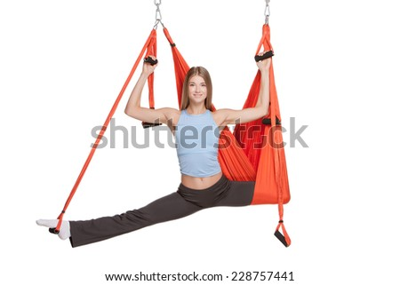 Young woman making antigravity yoga exercises with red hammock on a white background