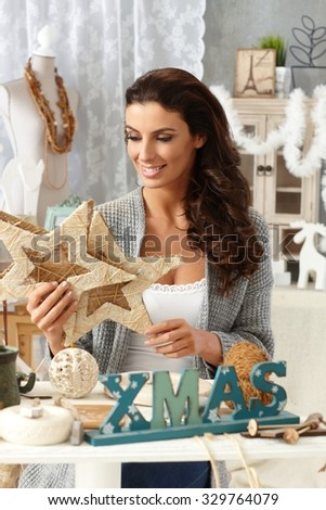 Young woman making christmas decoration, smiling happy. - stock photo