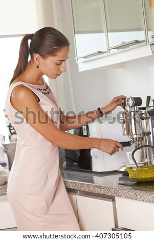 Young woman making coffee in classic coffee machine
