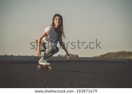 Young woman making downhill with a skateboard - stock photo