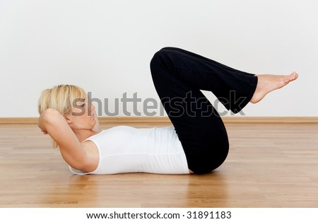 Young woman making excercises at home on wooden floor - stock photo