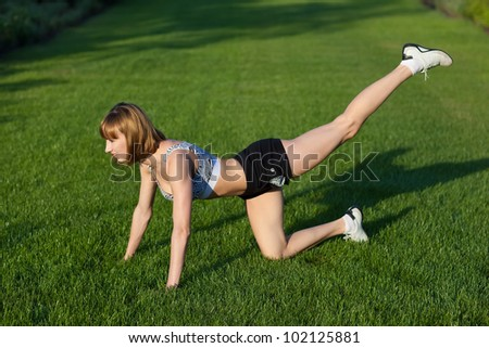 Young woman making fitness exercises, outdoor - stock photo