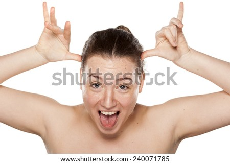 Young woman making funny faces with hands on head
