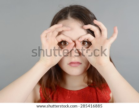 Young woman making hand gestures, looking through binoculars