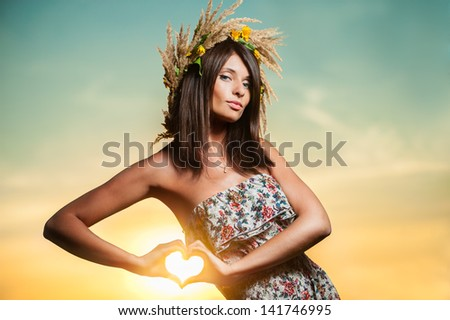 Young woman making heart shape with her hands on sunset background. - stock photo