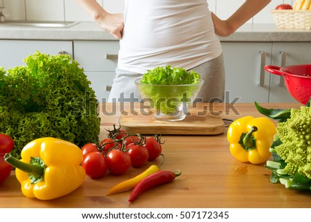 young woman making salad in the kitchen. Cooking healthy food at home