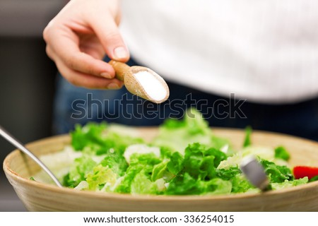 Young woman making salad in the kitchen. Pouring salt. - stock photo