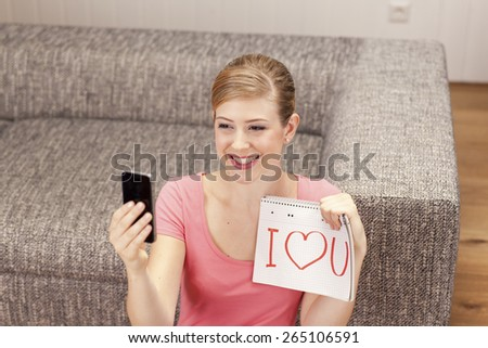 Young woman making selfie, I love you on notepad, smiling - stock photo