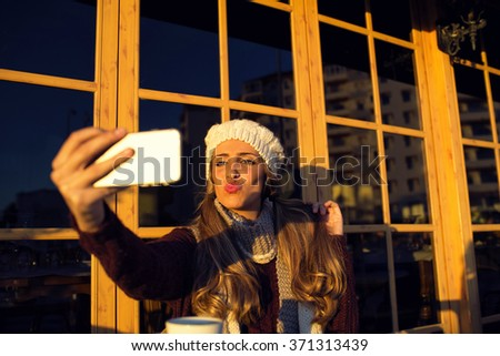 Young woman making selfie on her phone throwing a kiss out while sitting in cafe outdoors - stock photo