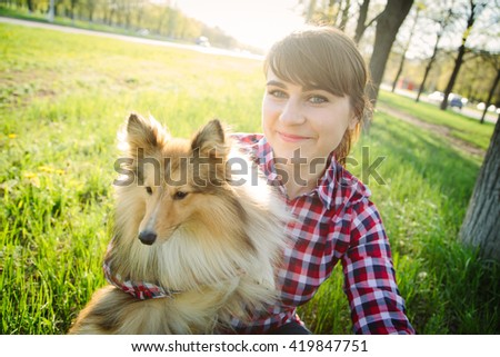 Young woman making selfie with her dog sheltie in the park on the green grass shetland sheepdog - stock photo
