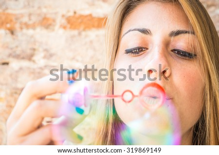 young woman making soap bubbles.  - stock photo