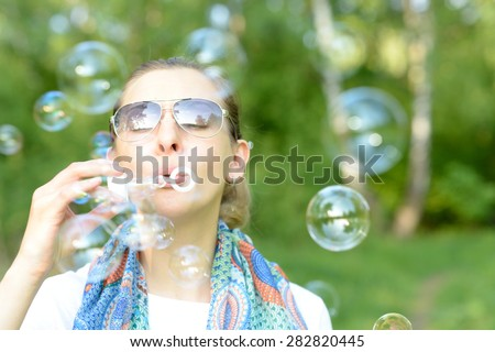 Young woman making soap bubbles outdoor