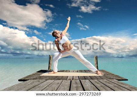 young woman making yoga exercise at a sea - stock photo