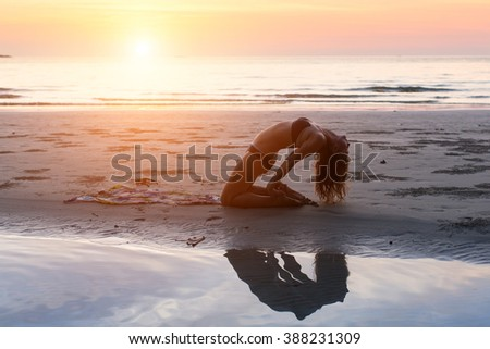 Young woman making yoga exercises on the beach in the setting sun. - stock photo