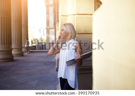 Young woman manager of big company calls via mobile phone and holds laptop computer during her work break, pretty female student stands near her university and talks via cell telephone with classmate - stock photo