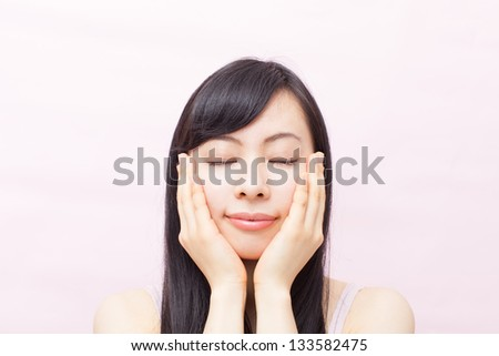 young woman massaging her face against pink background - stock photo