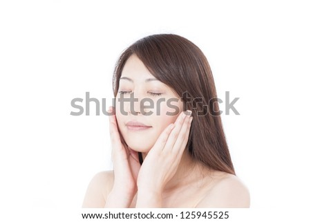 young woman massaging her face, isolated on white background - stock photo