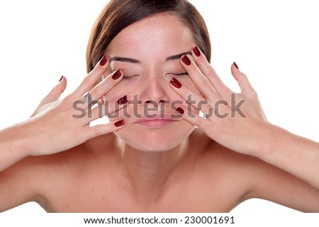 young woman massaging her face on a white background - stock photo