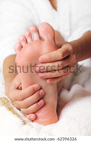 Young woman massaging her feet - stock photo