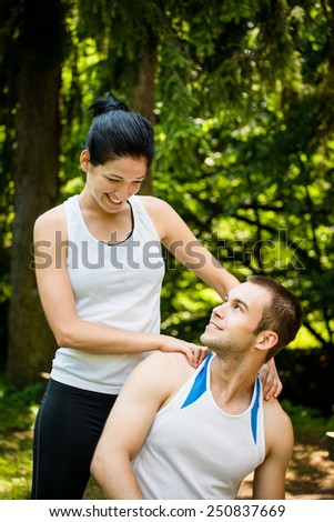Young woman massaging her friend after sport training in nature - stock photo