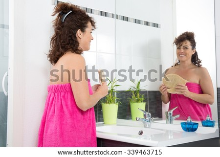 Young woman massaging skin with exfoliating glove.  Skincare concept.