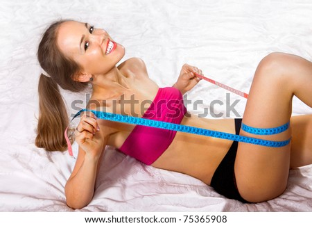 Young woman measures her body on white fabric - stock photo