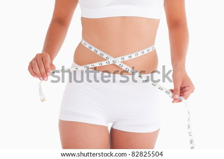 Young woman measuring her waist in a studio